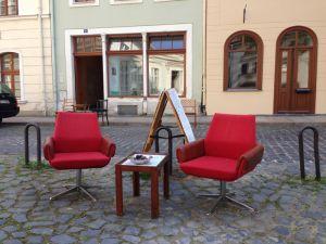 zwei rote Sessel und ein Tisch auf der Strasse