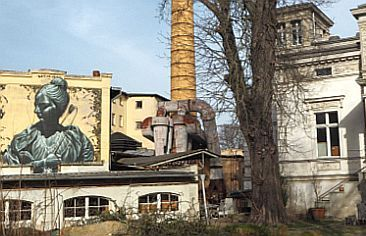 Industrial area with graffiti, chimney and villa